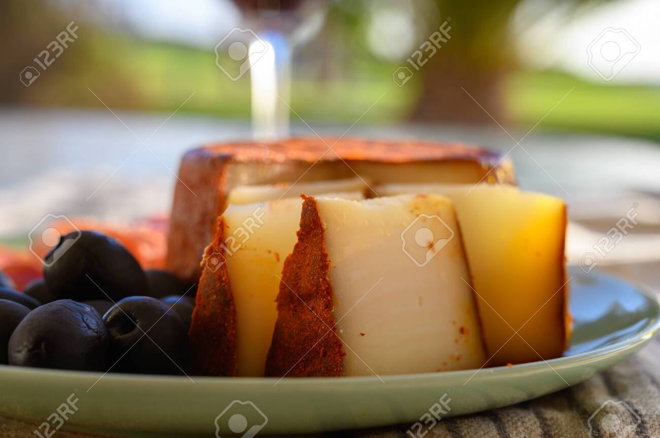 Tastes of Spain, jamon iberian, black olives and manchego cheese with red paprika close up in sun lights - 136528241