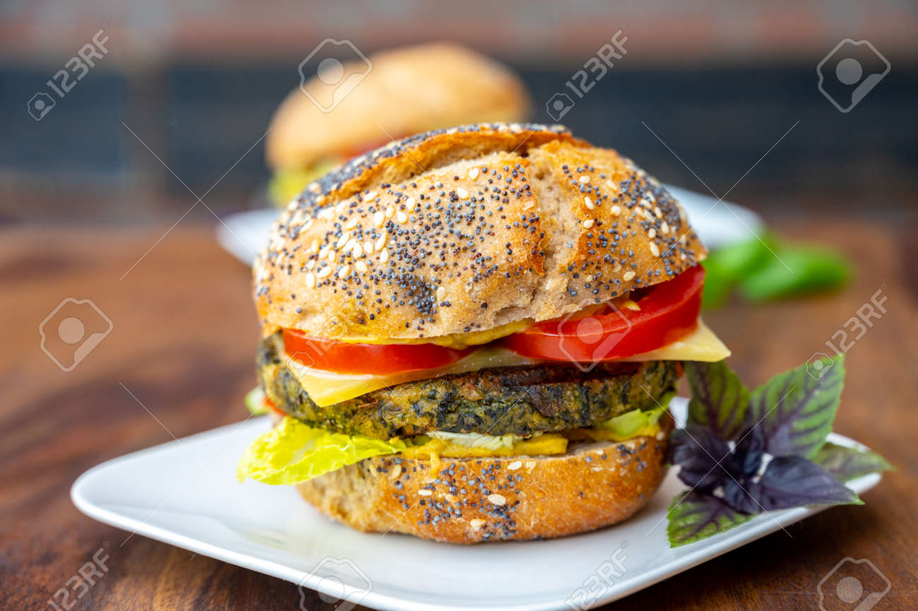 Eating of fresh and healthy vegetarian burgers with grilled spinach or pumpkin burgers, organic buns and vegetables close up - 155595771