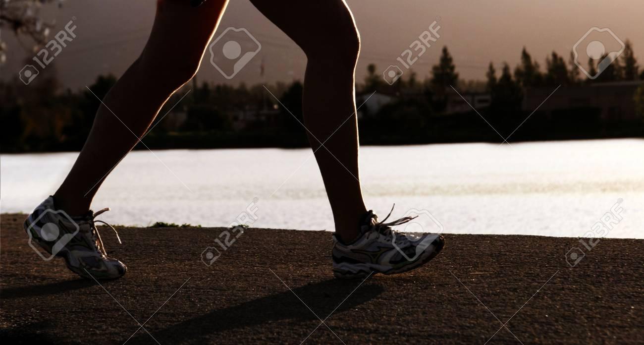 woman jogging along a river at sunset Stock Photo - 347398