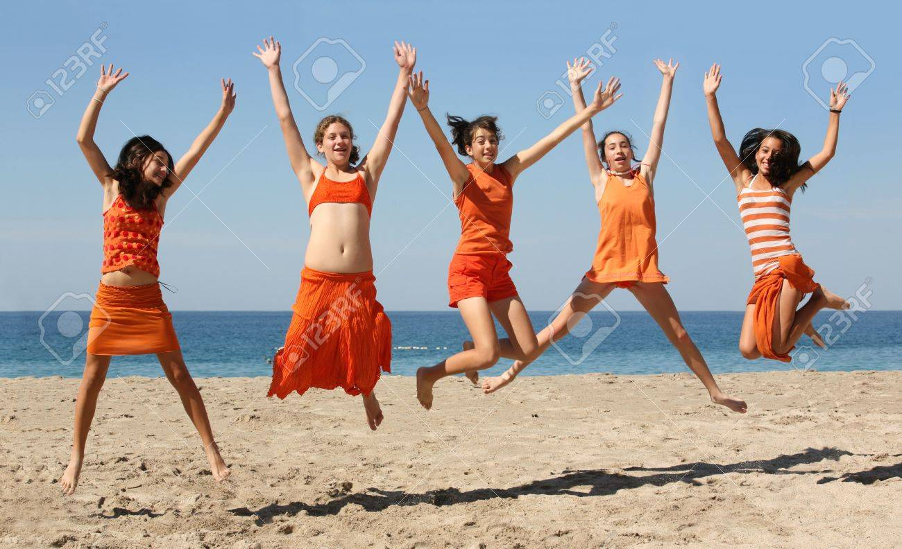 Five girls in orange clothes jumping on the beach Stock Photo - 639335