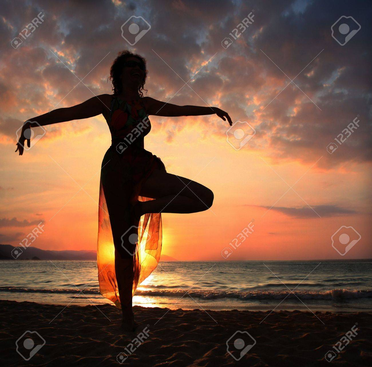 Woman doing yoga exercise on the beach at sunset, silhouette Stock Photo - 3974442