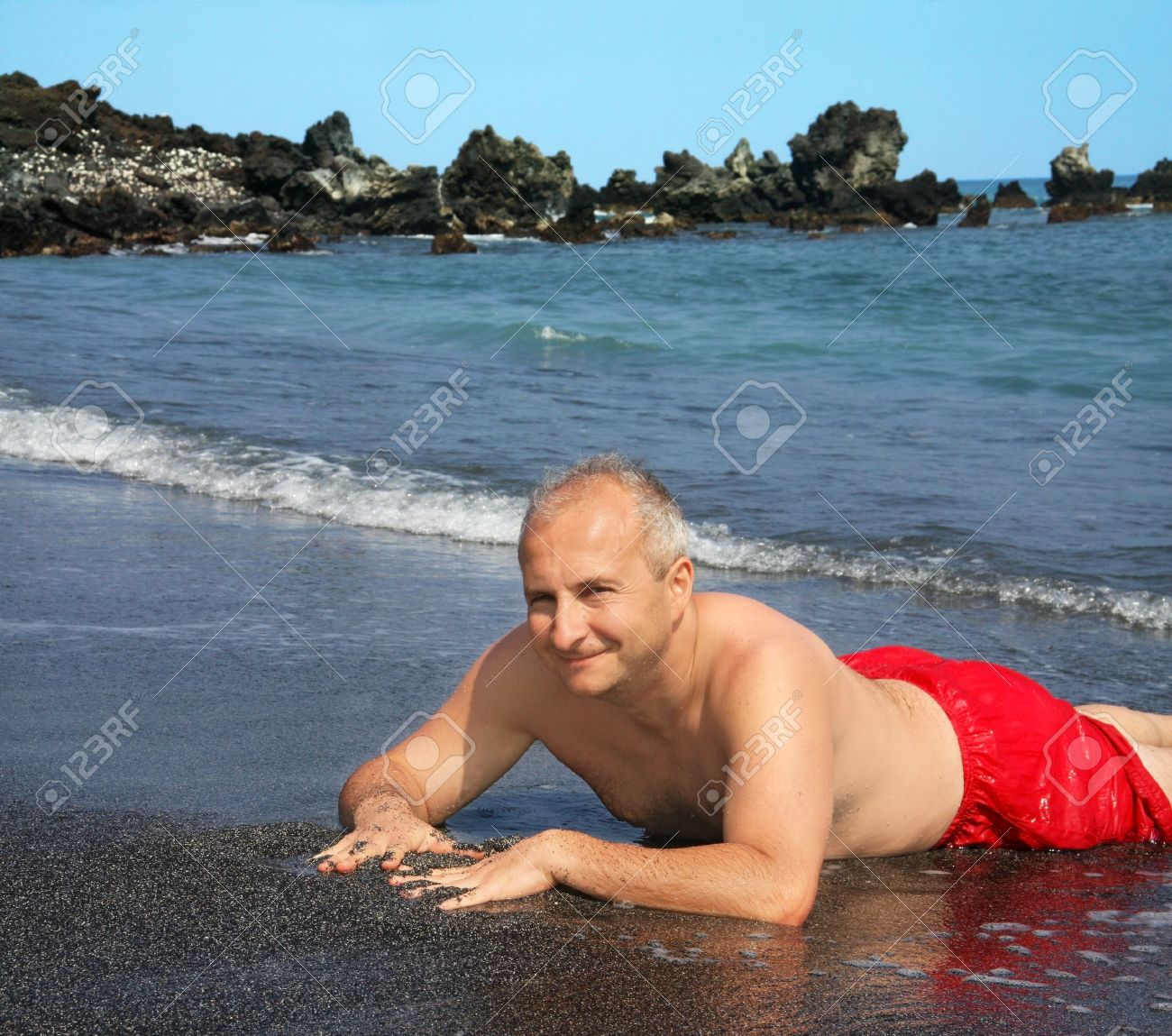 mature man on a black sand beach on big island, hawaii stock photo