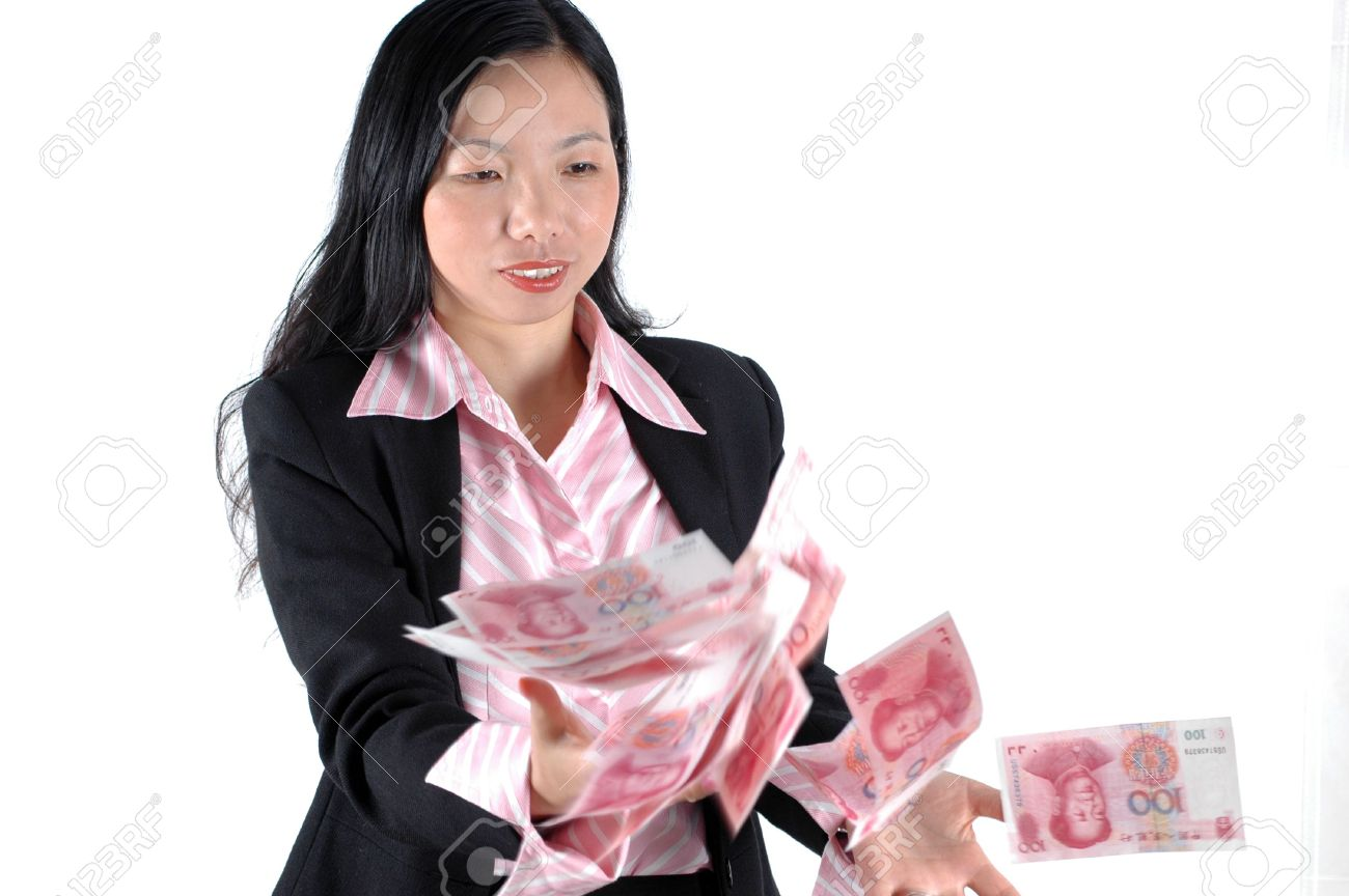 Young, Asian businesswoman throwing money, Chinese RMB banknotes, wearing lady's suit and shirt. Stock Photo - 3714252