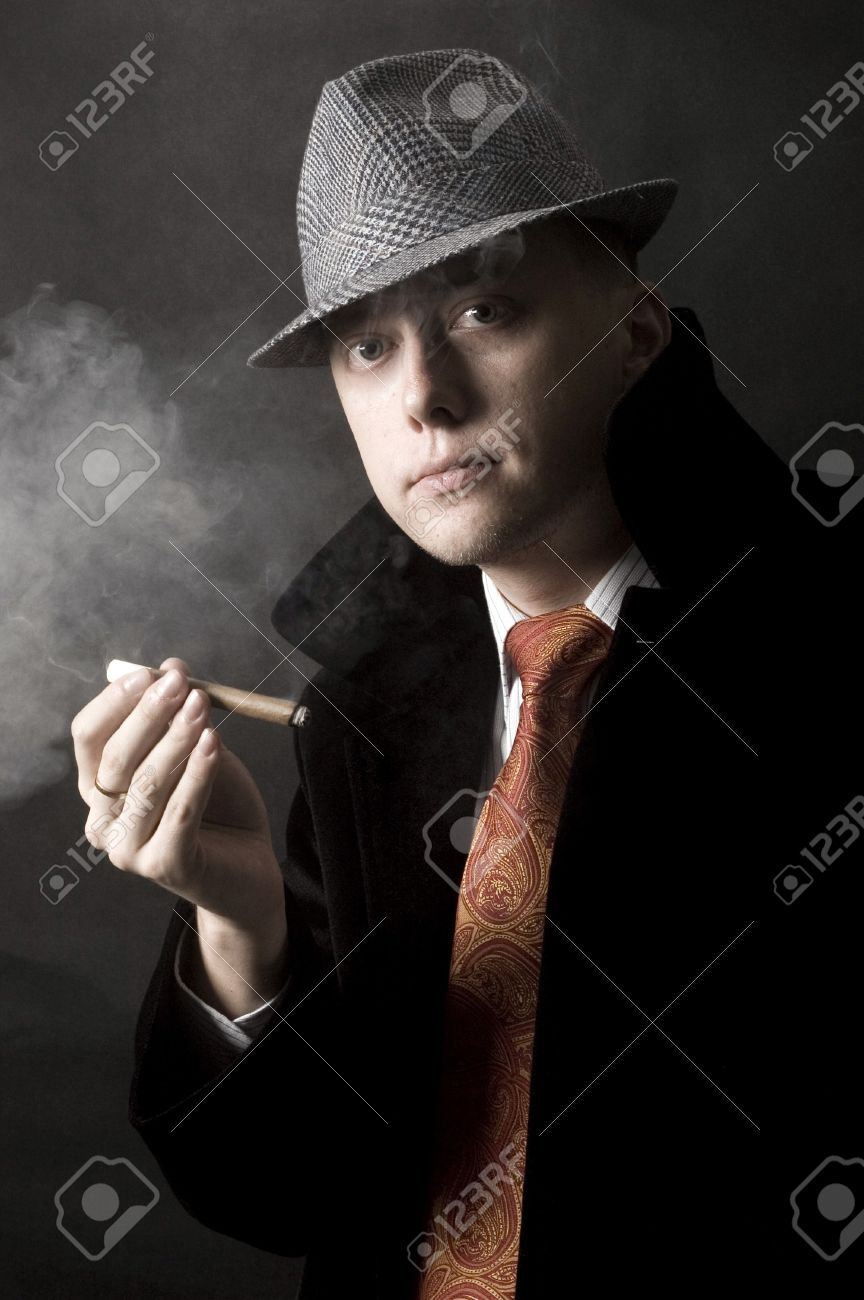 Young European gentleman with elegant clothes, tie and coat, wearing stylish hat. Smoking cigar. Stock Photo - 7618341