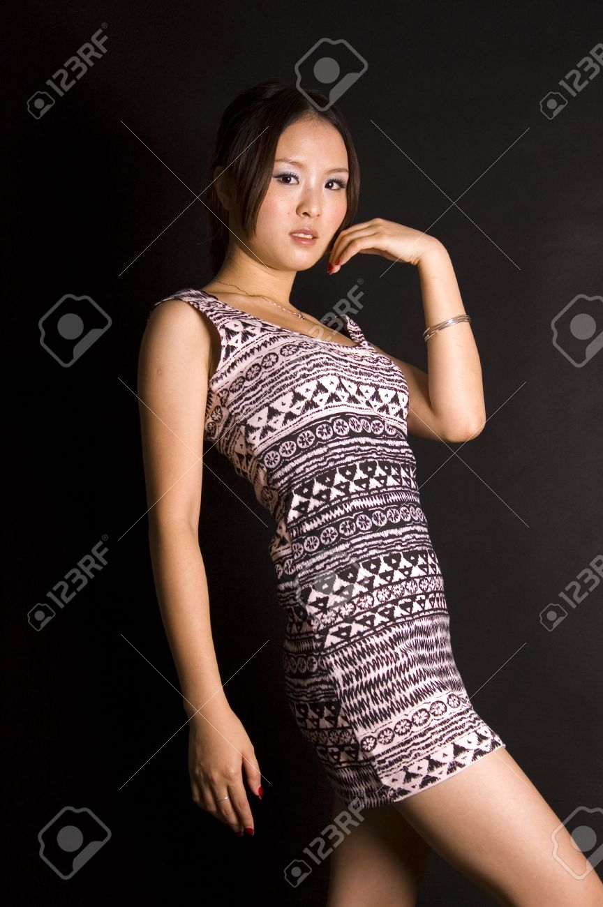 Cute Chinese teenager wearing short skirt, young and fashionable. Pretty Asian female model with black background. Stock Photo - 8471782