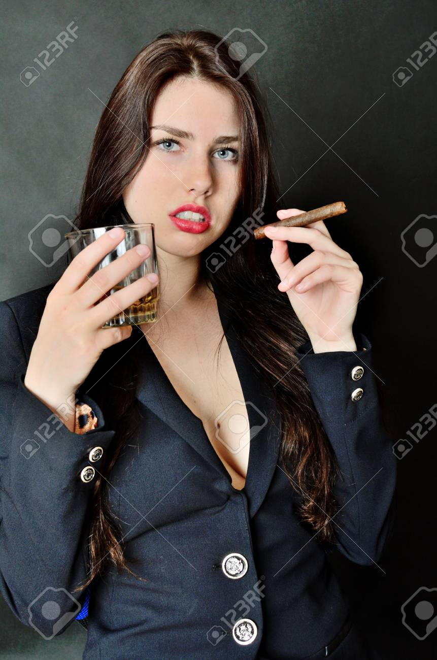 ad5b7de5d4 Pretty brunette model holding glass of whisky and cigar. Girl with  confident face expression