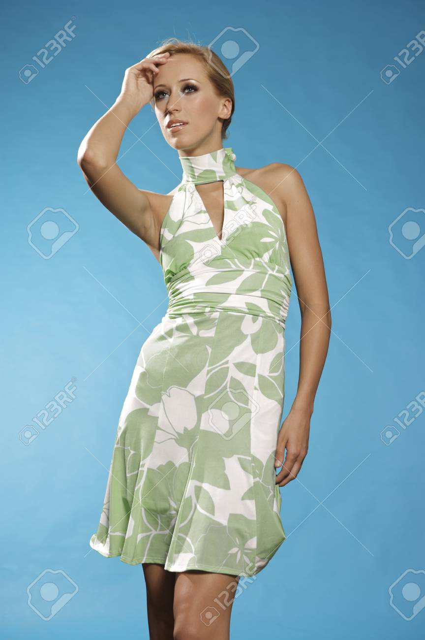 Young blonde woman posing in stylish dress on blue background Stock Photo - 9695028