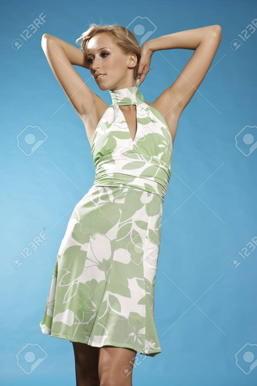 Young blonde woman posing in stylish dress on blue background Stock Photo - 9695024