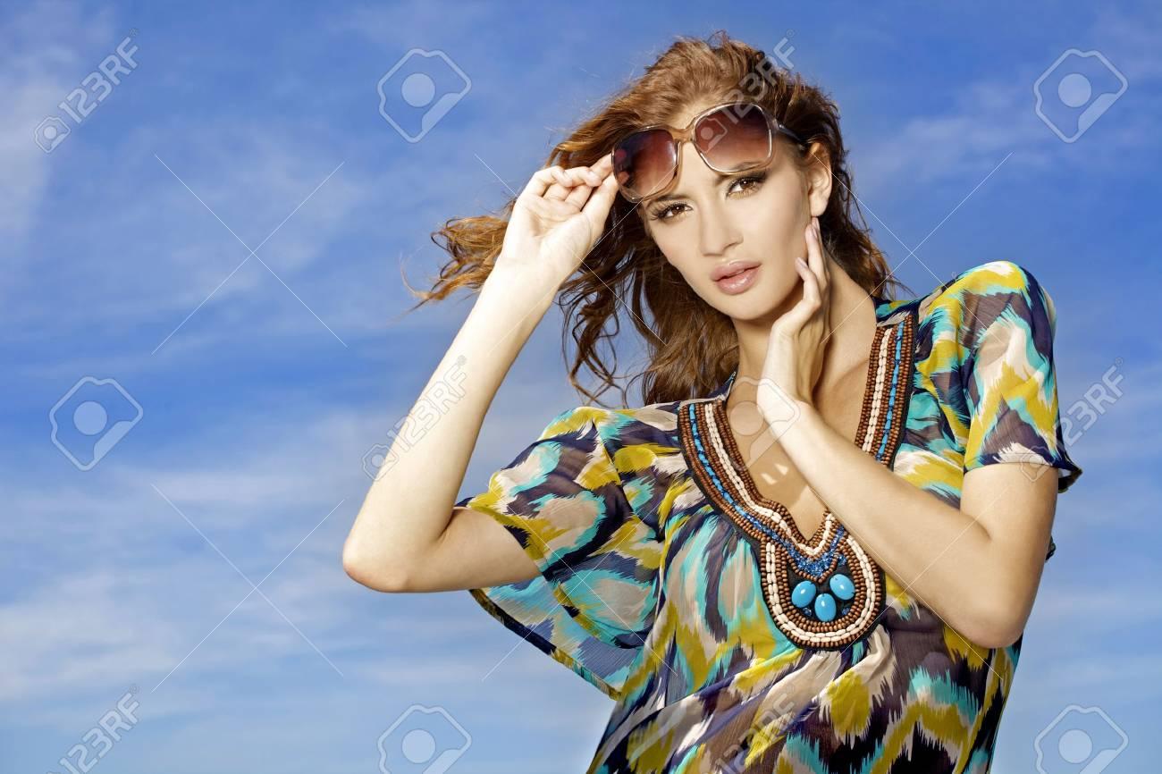 portrait of beautiful brunette girl in sunglasses on background blue sky Stock Photo - 9696001