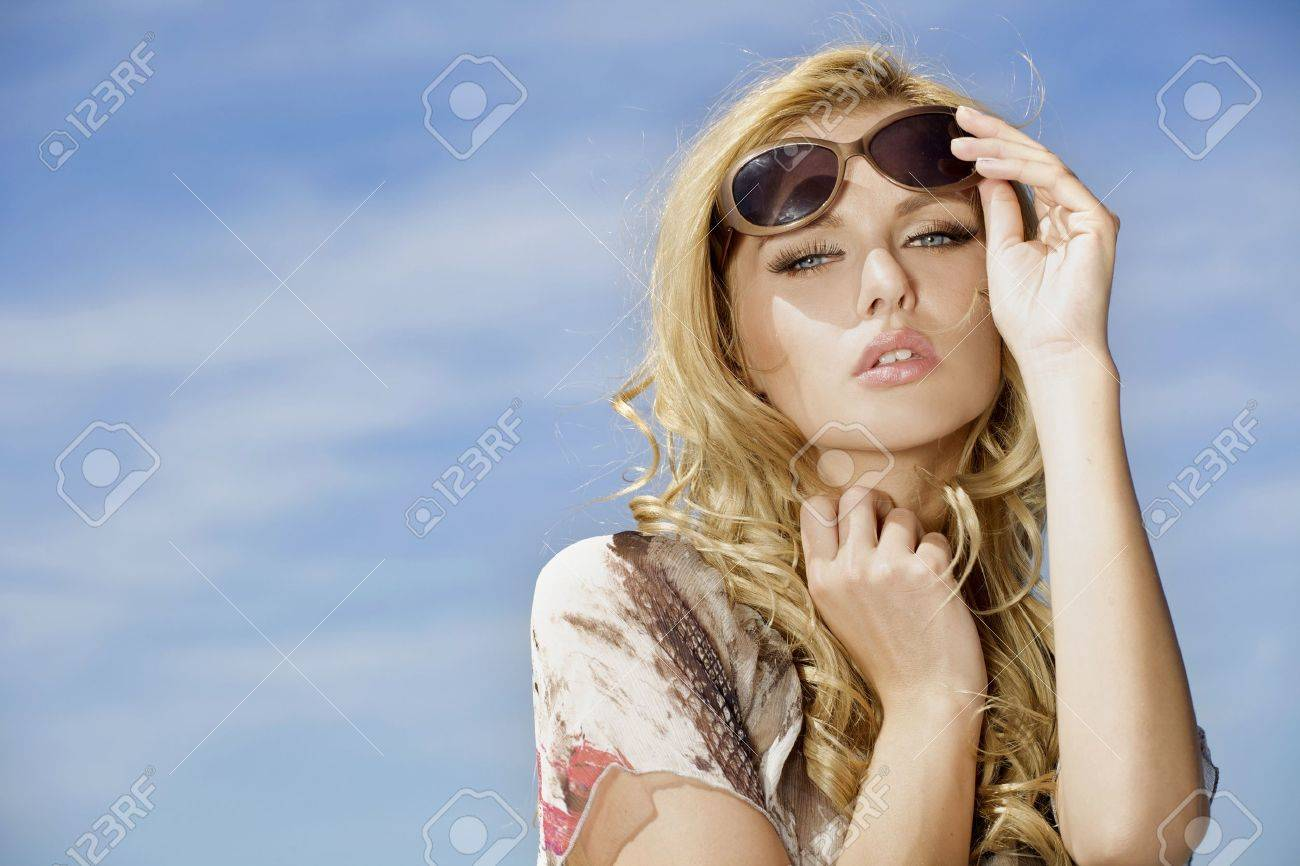 portrait of beautiful blonde girl in sunglasses on background blue sky Stock Photo - 9912267