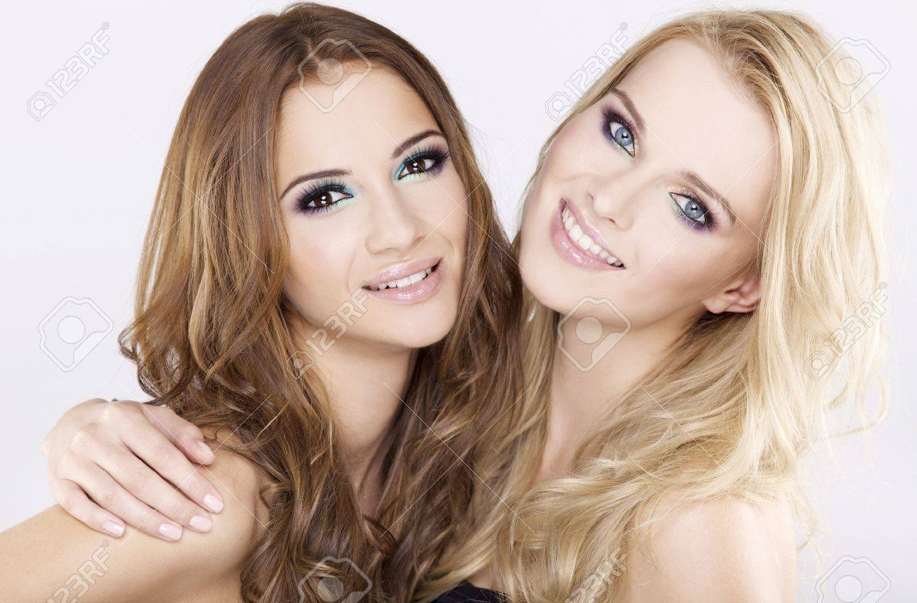 Two smiling attractive girl friends - blond and brunette on white background Stock Photo - 11781772