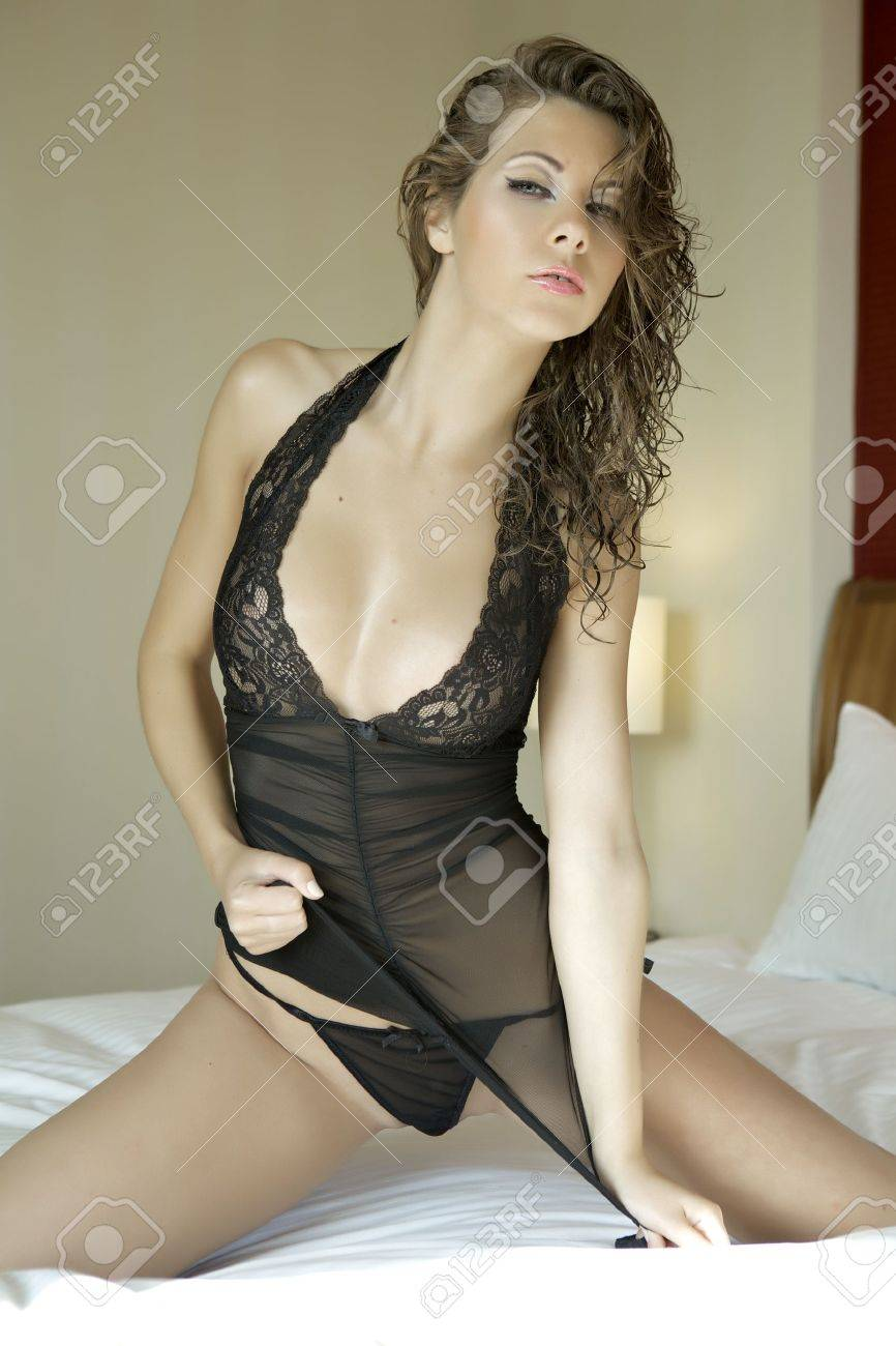 Beautiful and sexy brunette young woman wearing black lingerie in bed Stock Photo - 13780906