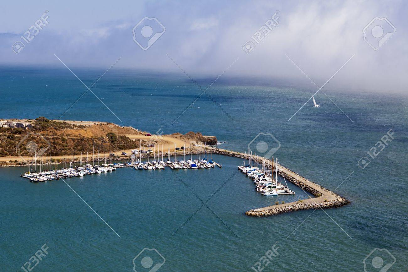 Fog rolls into San Francisco Bay and toward small boats moored in Horseshoe Bay, near Sausalito and  just east of the Golden Gate Bridge. Stock Photo - 10627995