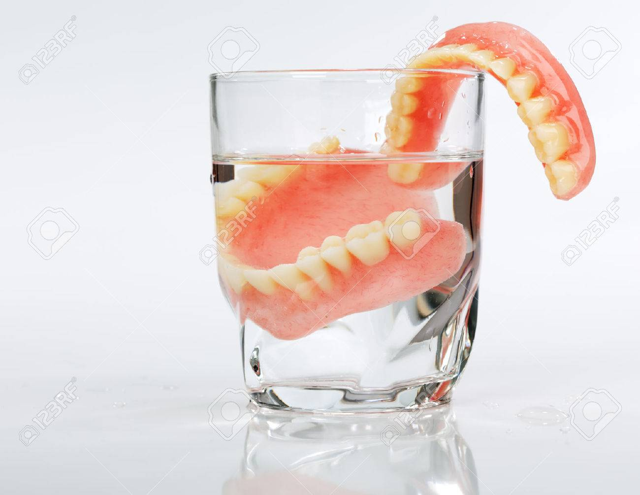 A Set Of Dentures In A Glass Of Water On A White Background Stock Photo,  Picture And Royalty Free Image. Image 26352319.