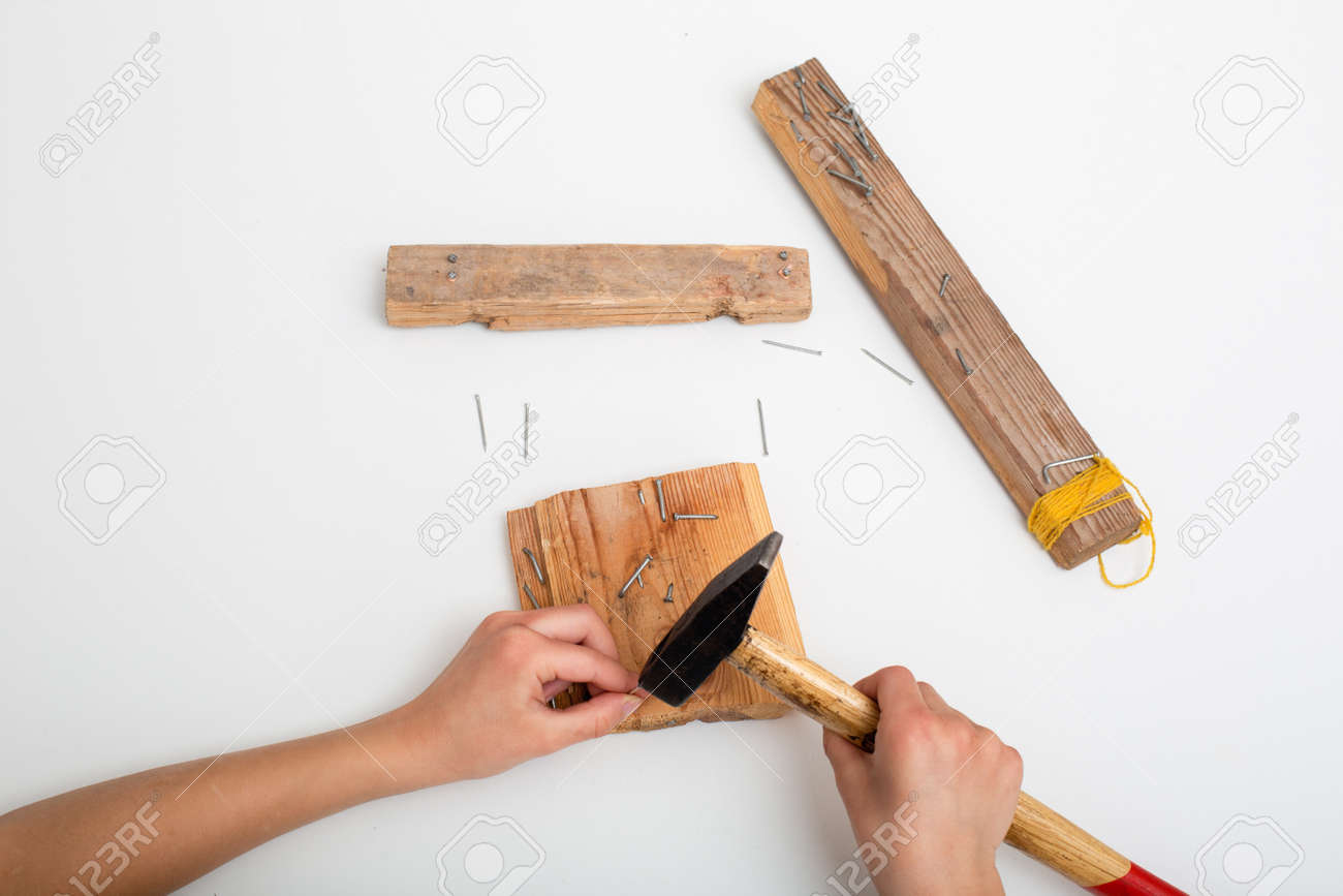 child hand with pliers and hammer on a white table, view from above - 167297632