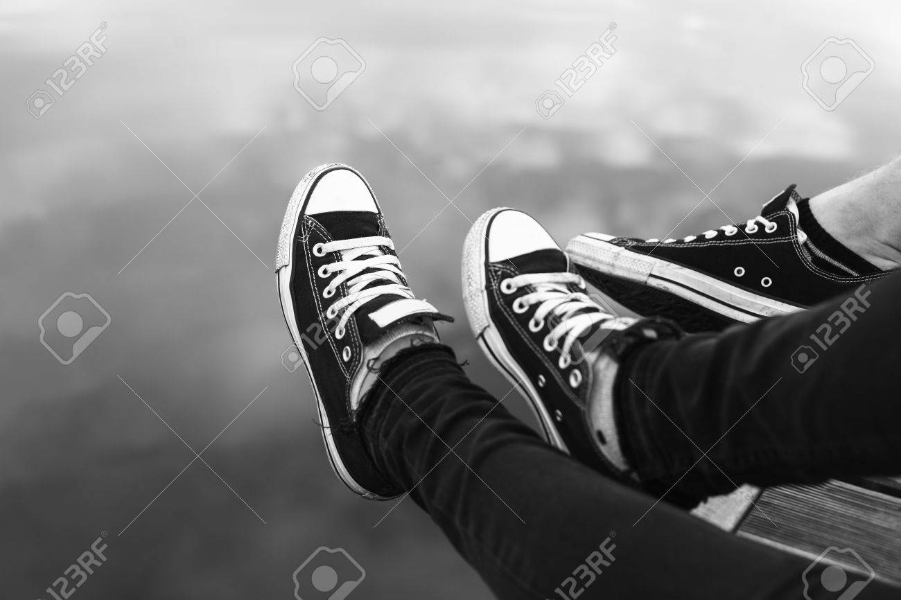 Couples feet in sneakers relaxing by the water black and white stock photo 66520081