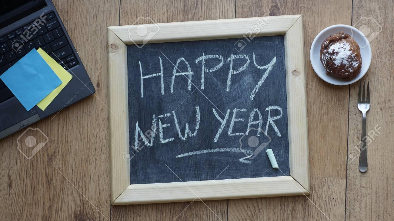Bonne année écrit sur un tableau à côté d un beigne néerlandais au