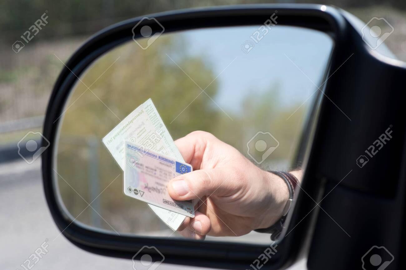 A man shows driver's license and vehicle registration during