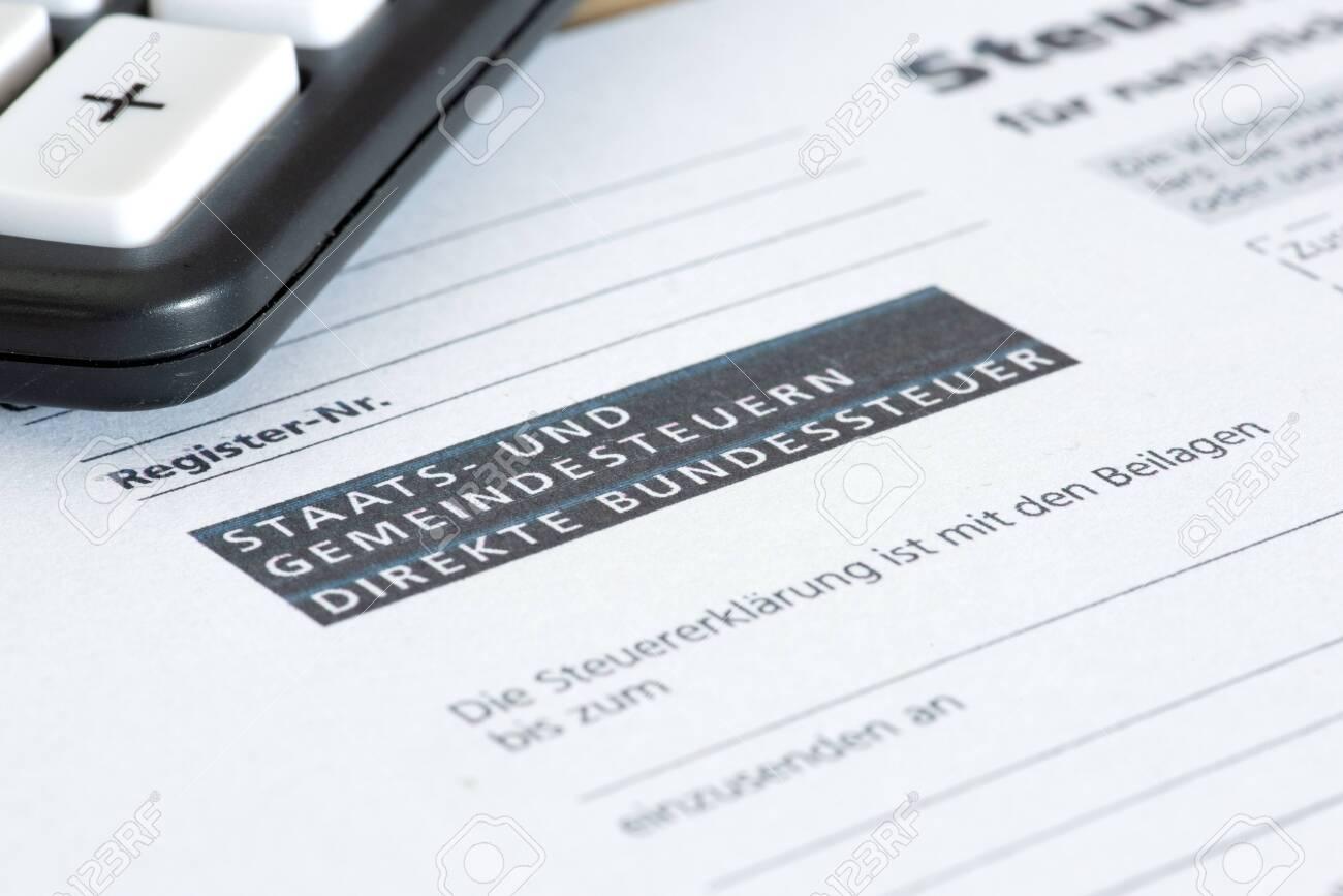 Swiss tax return form and a calculator - 153783664