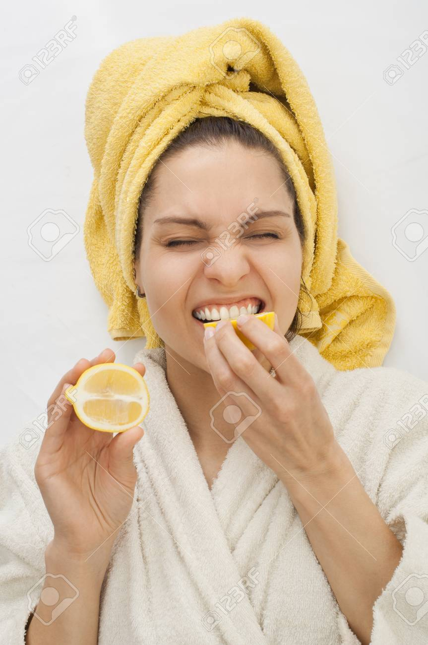 A Girl In A Dressing Gown Bites A Lemon, Frown, A Yellow Towel ...