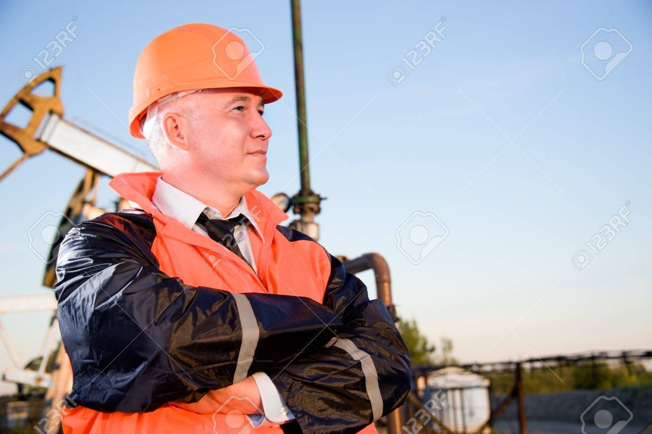 Oil worker in orange uniform and helmet on of background the pump jack and blue sky. Stock Photo - 10815444