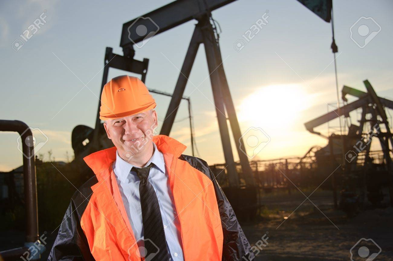 Oil worker in orange uniform and helmet on of background the pump jack and sunset sky. Stock Photo - 10815443