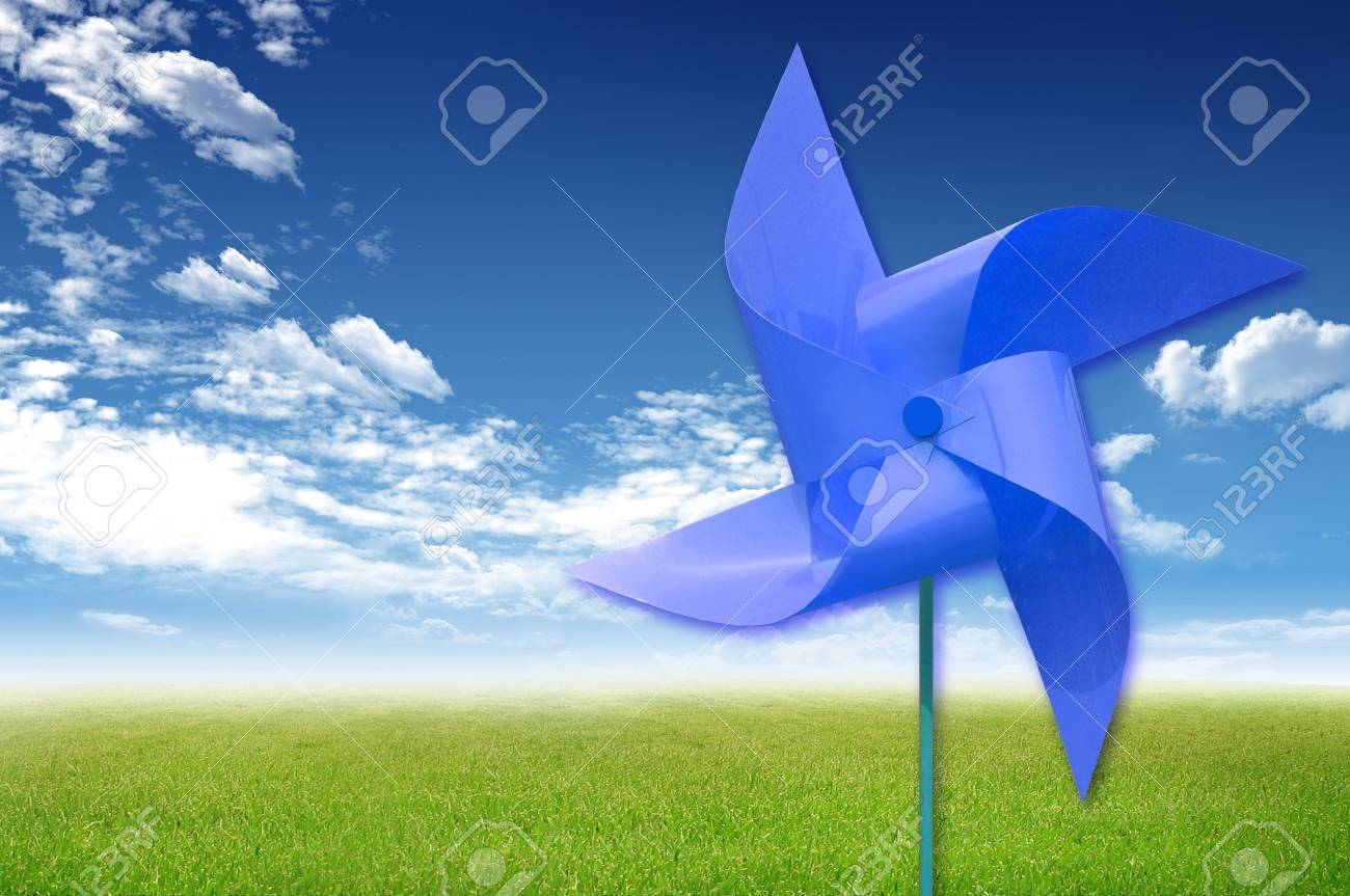 Colorful windmaill toy on the green grass and blue sky background, for ecology idea and concept Stock Photo - 10785430