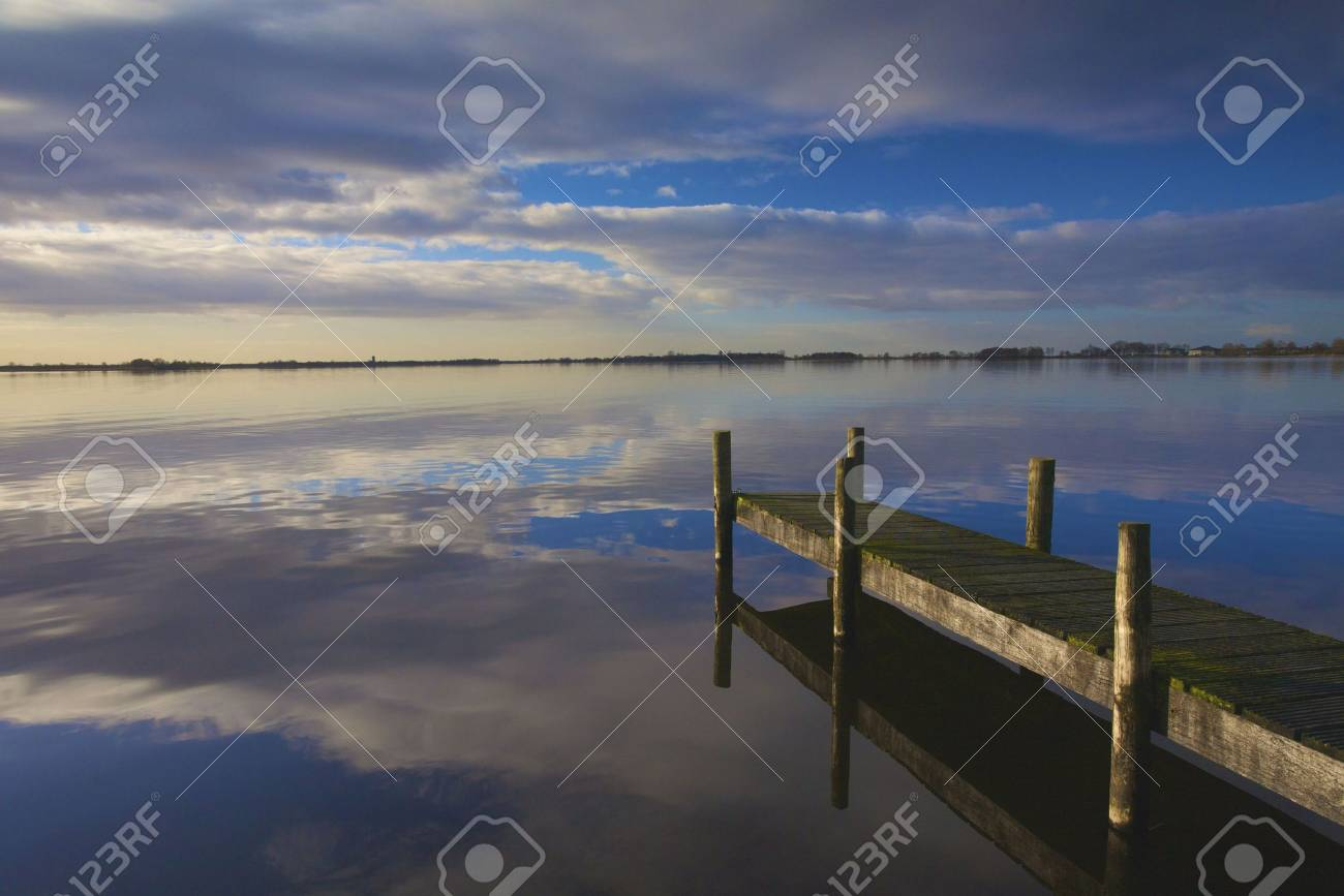 Landscape in Holland with a calm lake and sunset wit a jetty Standard-Bild - 5688219