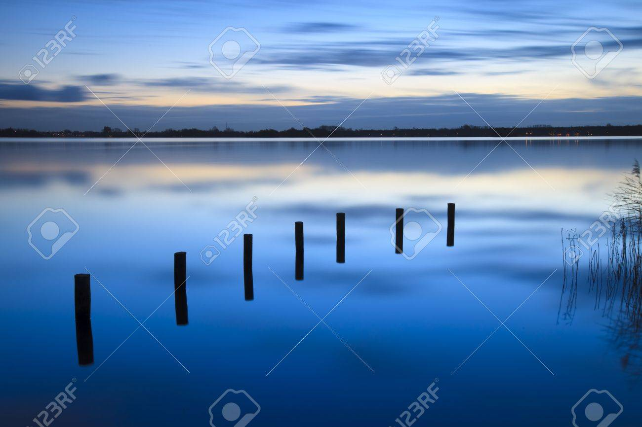 Calm sunrise over a lake with clouds reflection in the water Standard-Bild - 6017691