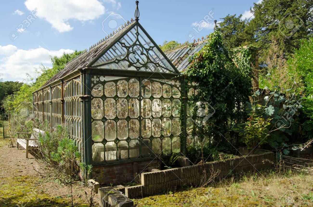 view of an old victorian cast iron greenhouse in an un loved stock
