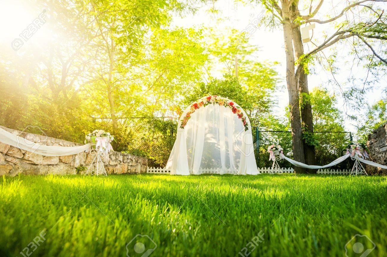 Wedding Arch with flowers on the grass - 14161953