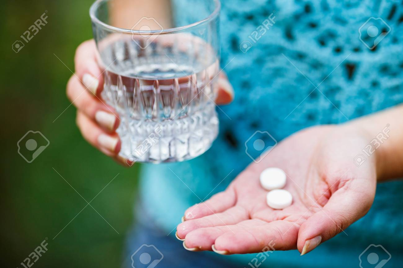 the girl holds a glass of clean water and two white pills - 97368613