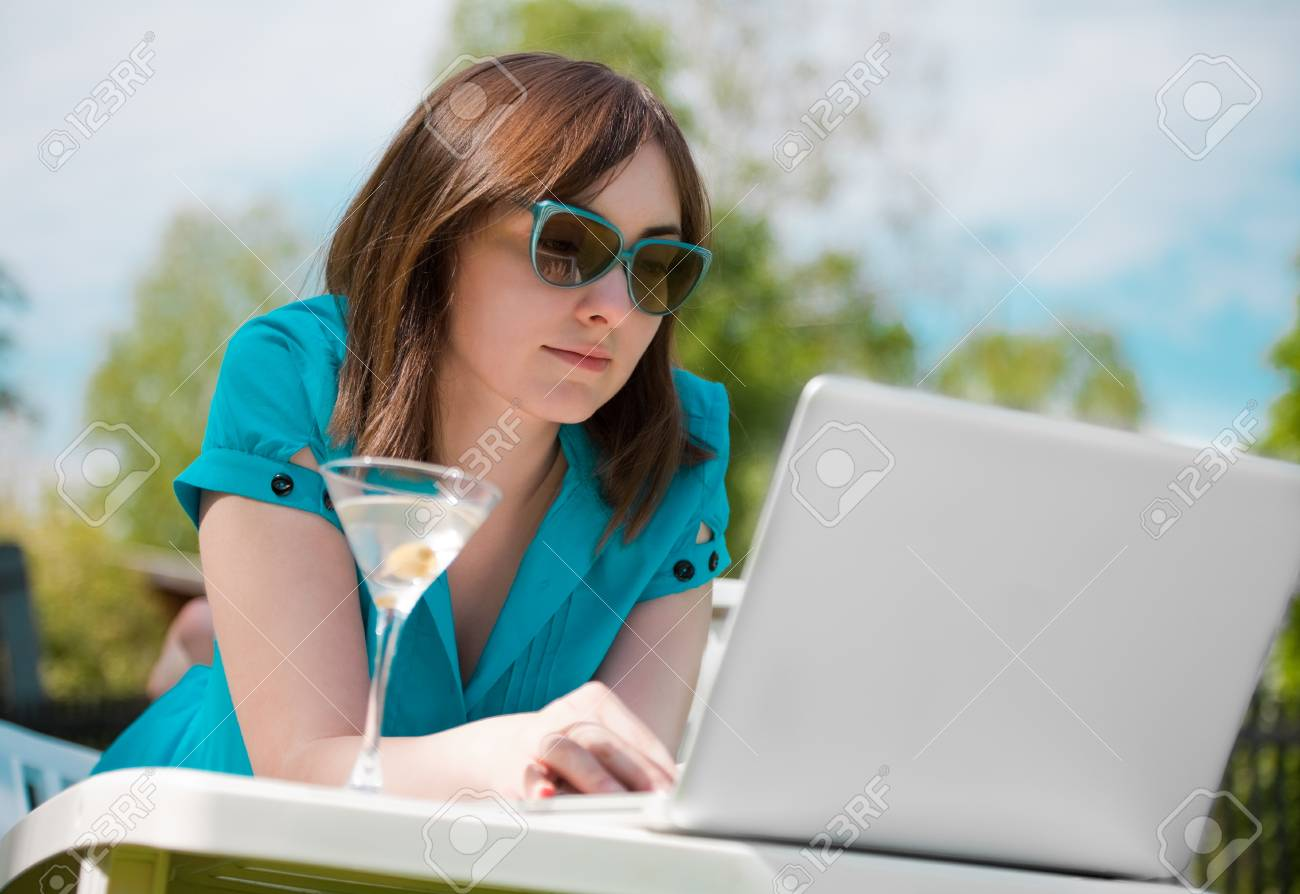 Businesswoman with laptop and glass of martini outdoors Stock Photo - 7367745