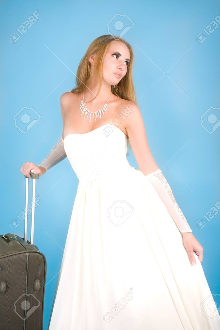 Bride with large suitcase standing on the blue background Stock Photo - 7489458