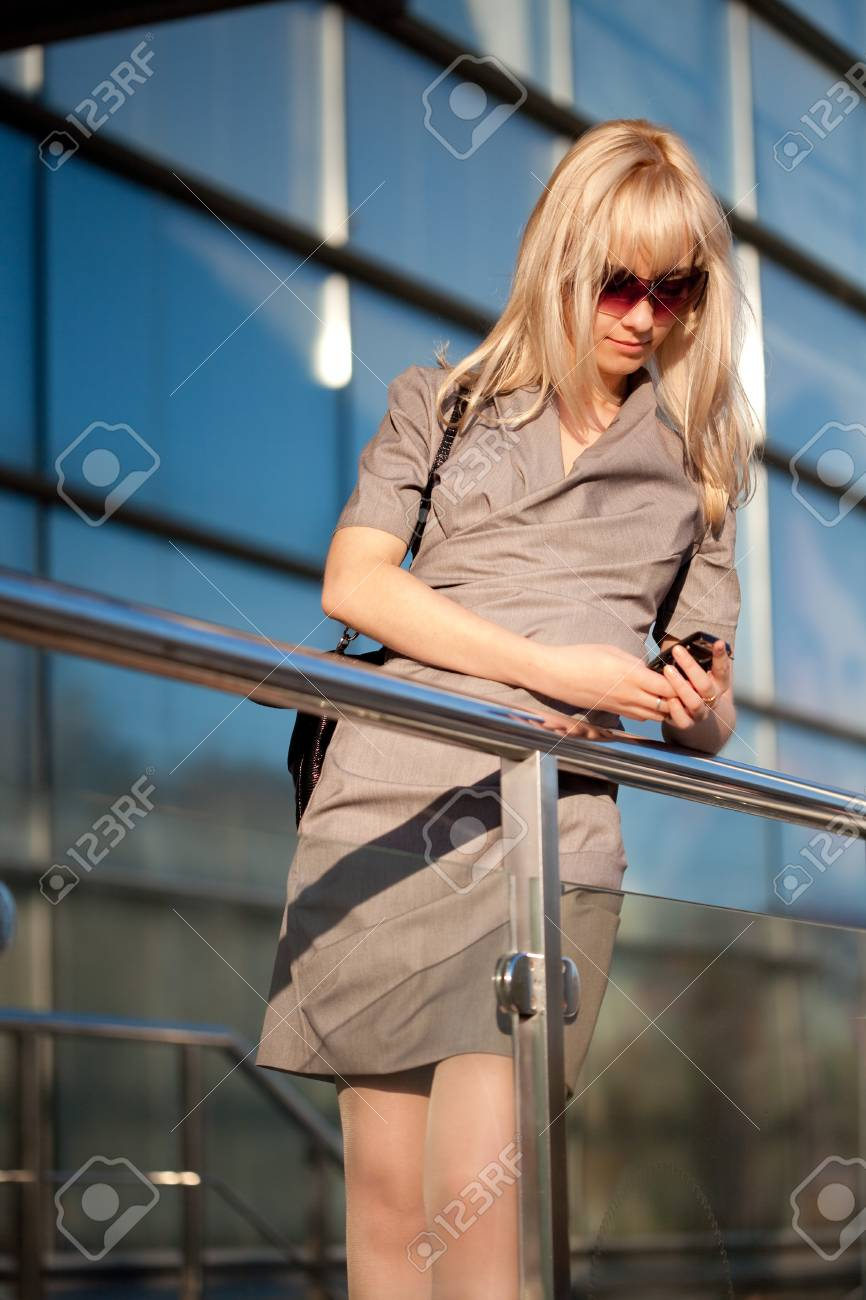 Beautiful woman in sunglasses with cellphone walking Stock Photo - 7551065