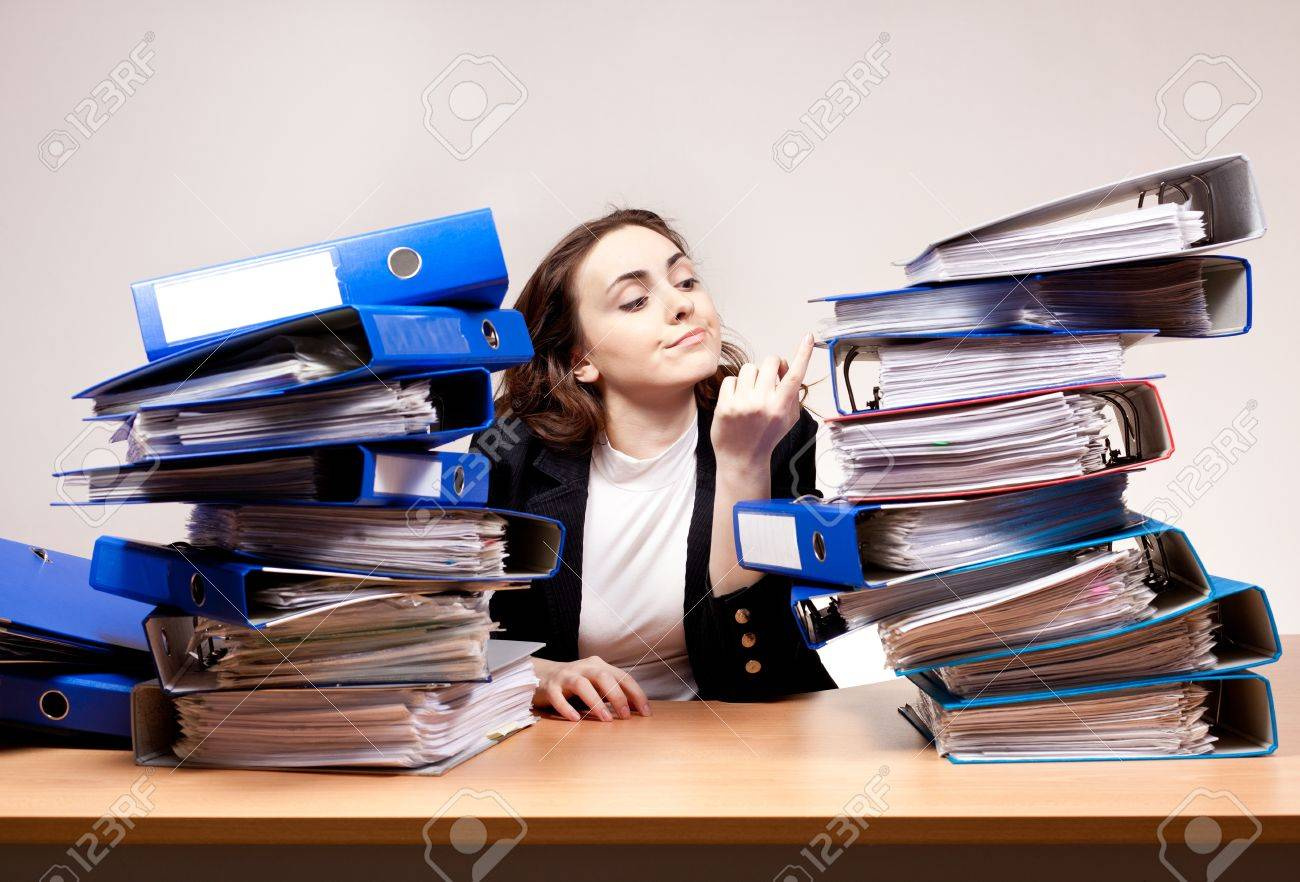 Frustrated businesswoman with stack of folders at office - 16578608