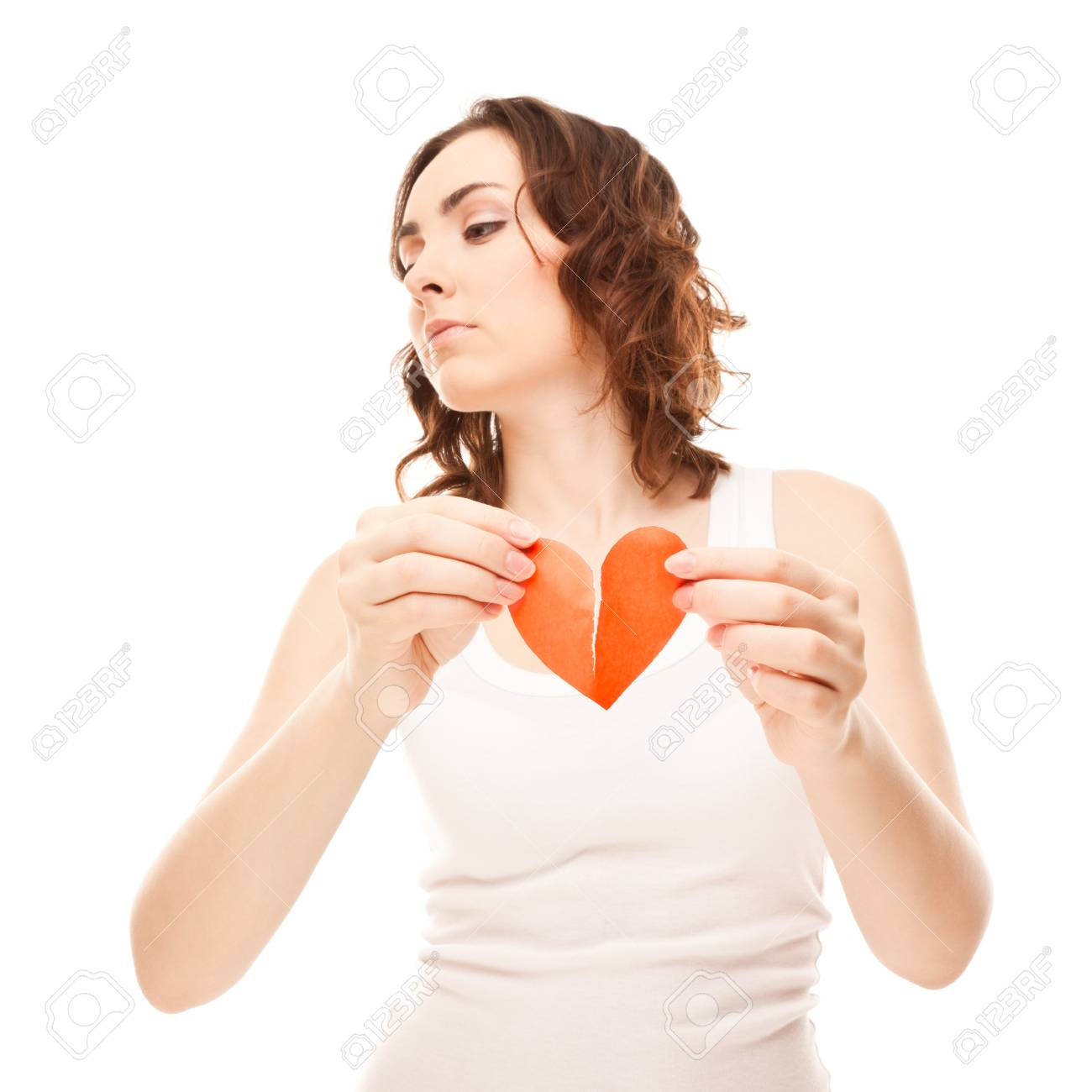 Attractive brunette young girl holding broken paper red valentine heart Stock Photo - 17573065