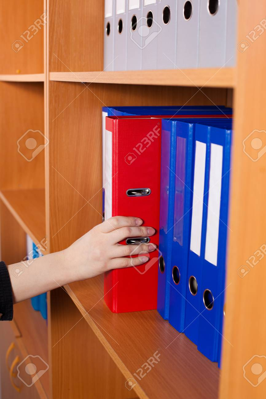 Woman's hand taking a red folder from shelf Stock Photo - 20952283