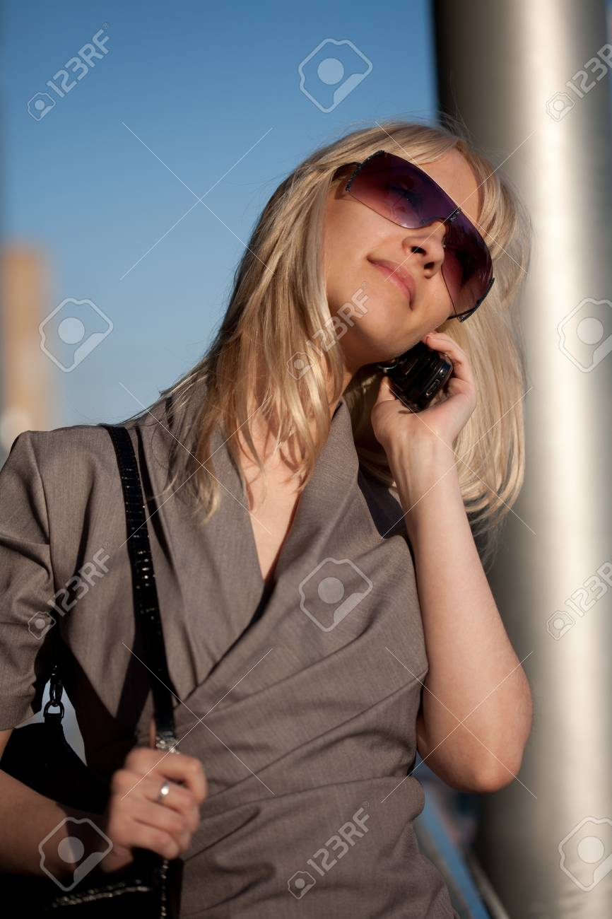 Beautiful woman in sunglasses with cellphone walking Stock Photo - 26748784
