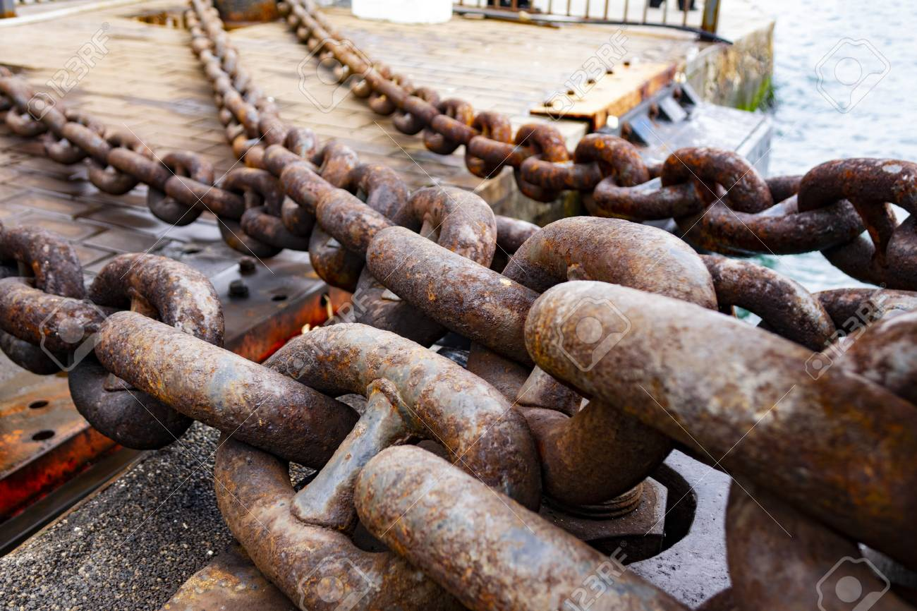 Close up of old rusty chain, industrial port with chainss, crane background out of focus, sunny day, industrial concept - 121143357