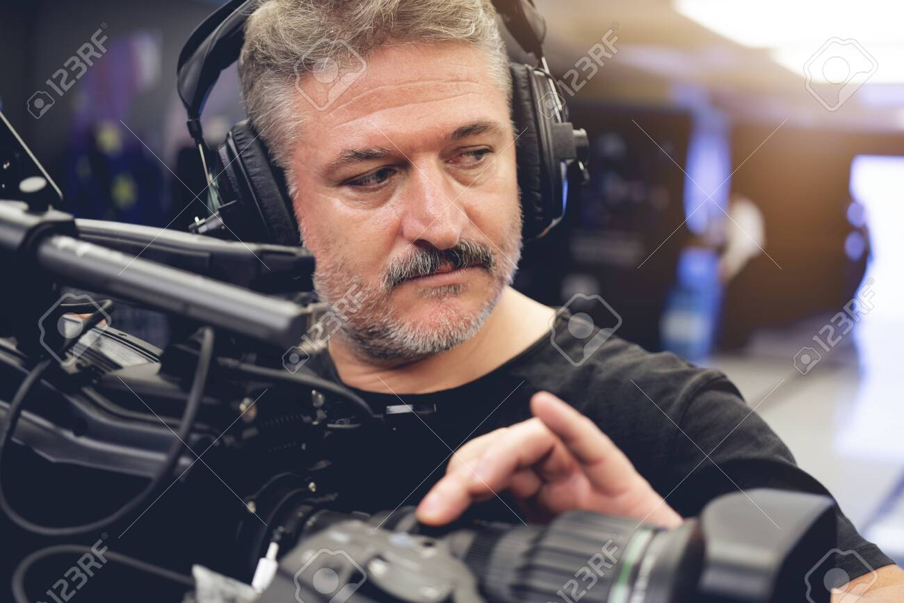 Professional cameraman with headphones with HD camcorder in live television - 135894806