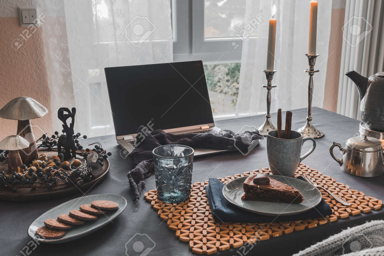 Table with laptop, cake, cookies and autumnal decoration in a cozy room prepared for virtual coffee with family or friends, useful during worldwide pandemic quarantine times - 162647058