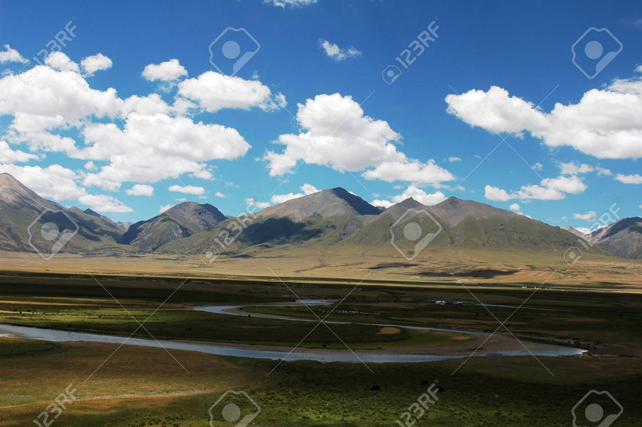 Landscape of mountains and meadows with a river under the blue sky and white clouds Stock Photo - 9133420
