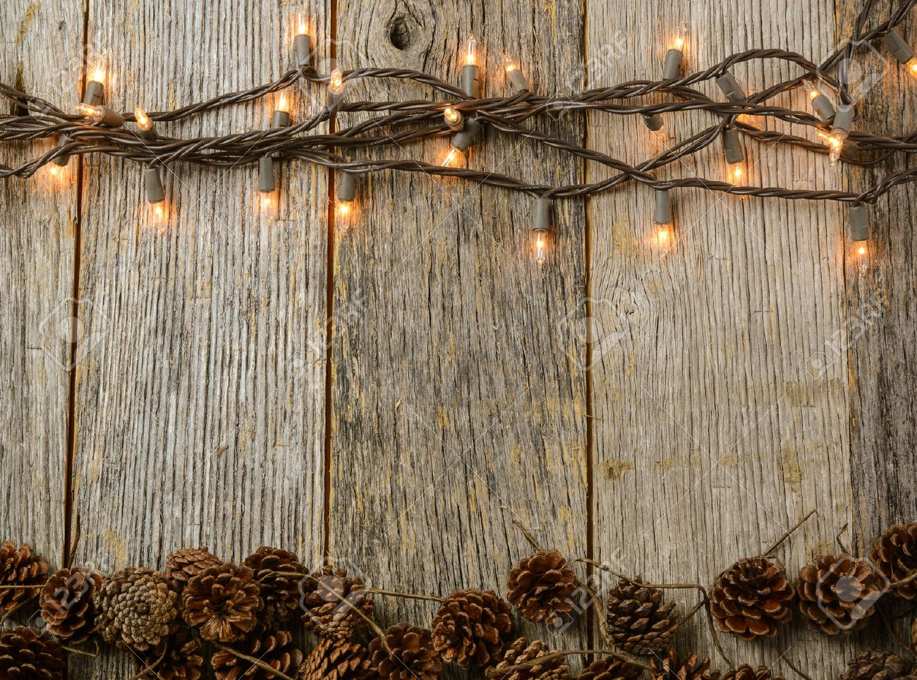 Christmas Lights And Pine Cones On Rustic Wood Background Stock ...