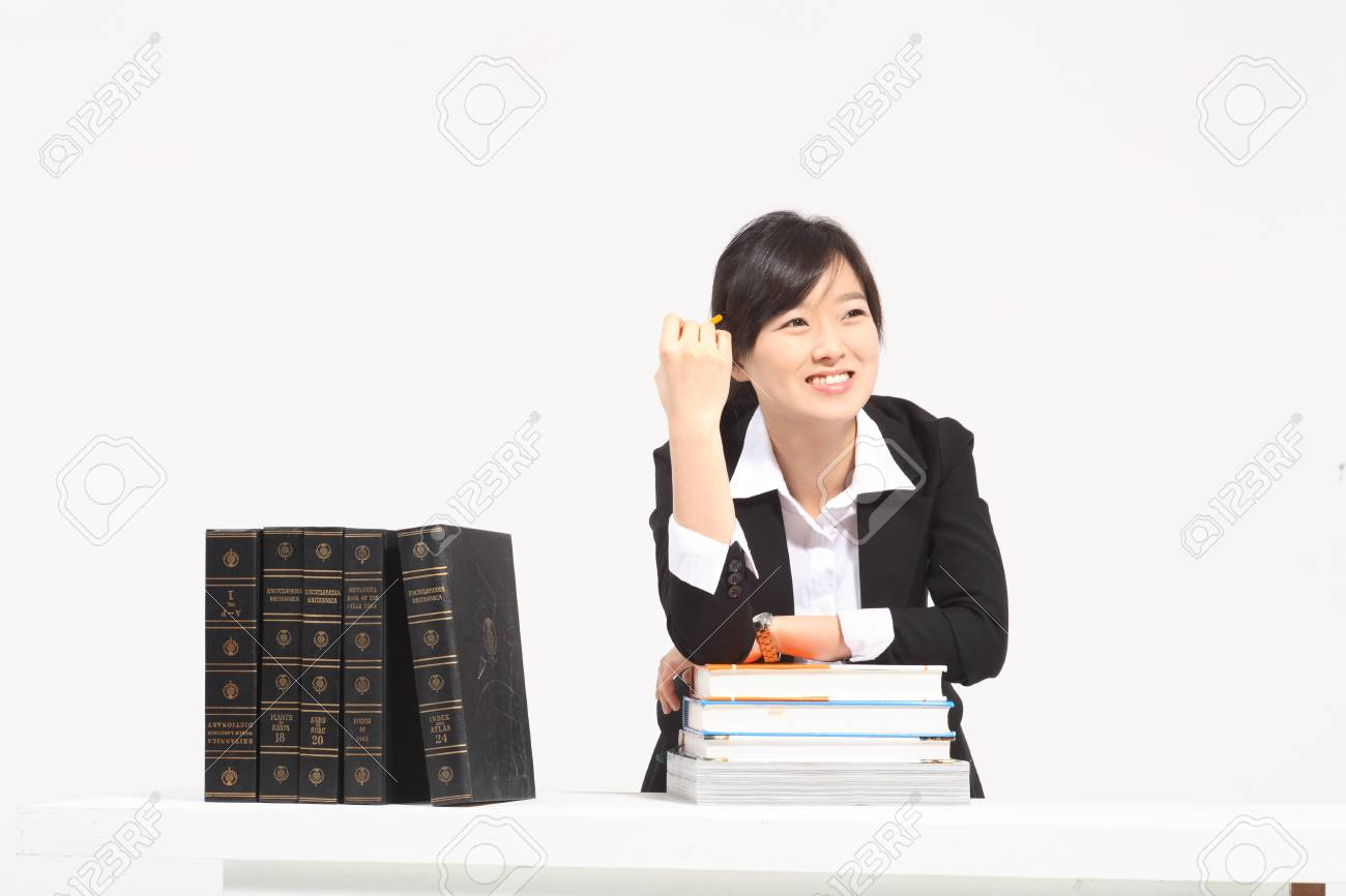A Woman Sitting At The Desk With A Book - Isolated On White Stock ...
