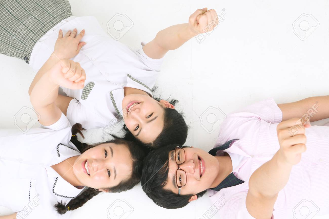 Two Asian Girls And A Boy Students Laying Down On The Floor And