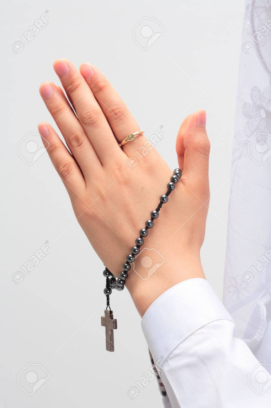 isolated shot of praying hands with a rosary in hands of a female