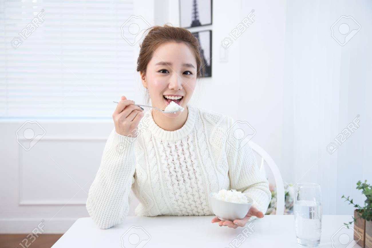 Young female Asian eating a bowl of rice in white interior room - 93530369
