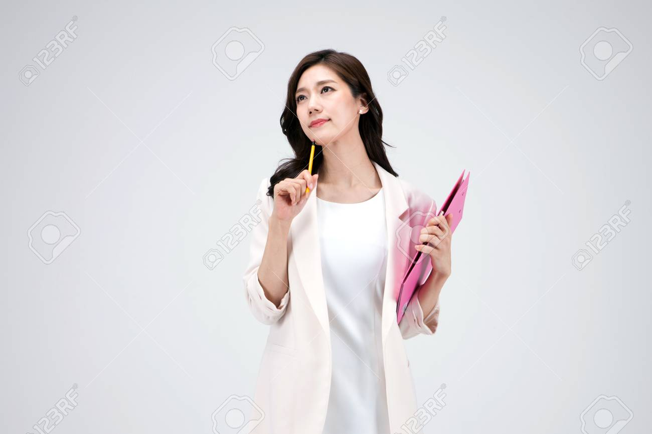 Isolated shot in studio - Asian career woman in white dress holding a file folder - 93530426