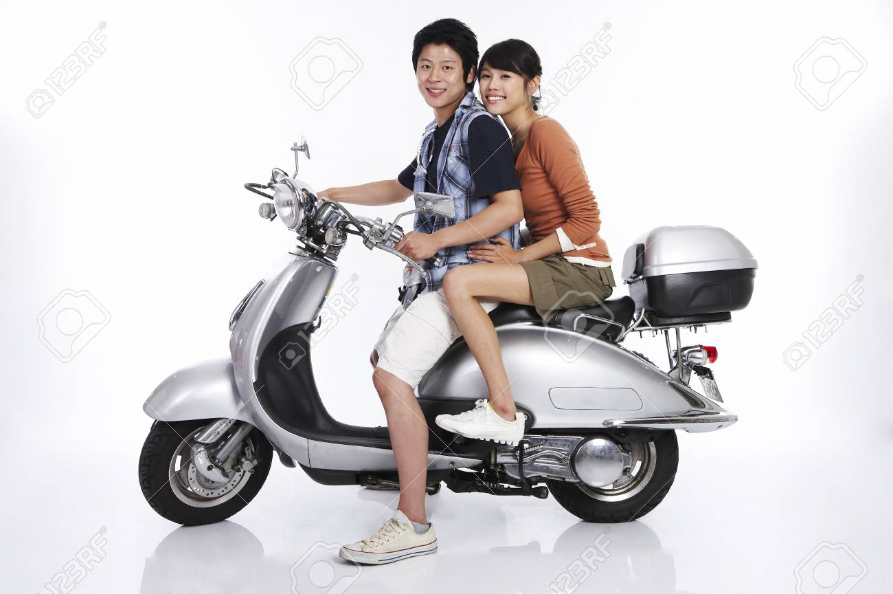 Asian couple posing in a white studio riding a motorcycle Stock Photo -  85243326